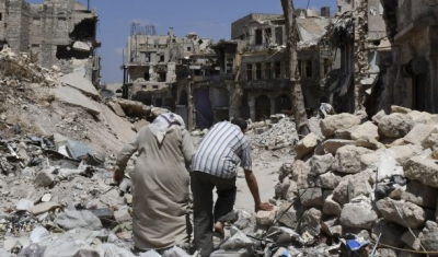 Two persons walk in the ruins of Aleppo, Syria