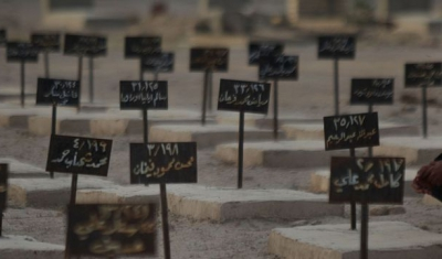 Man sitting in front of a graveyard (tombstones in arabic)
