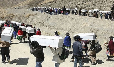 Group of people carrying coffins down the mountain