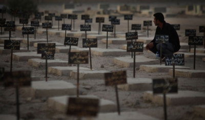 Iraq, Basra. A worker of the Al-Zubai centre tends to graves of recovered but unidentified casualties of war.