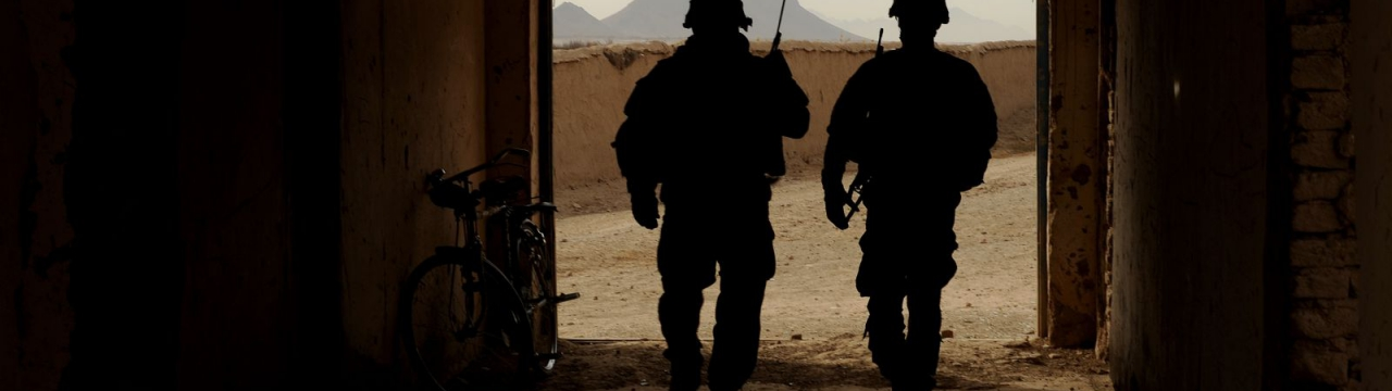 Two US soldiers walking out of a building