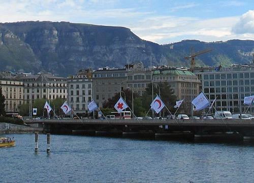 View of Geneva's Mont-Blanc Bridge with flags of the International Committee of the Red Cross (ICRC)