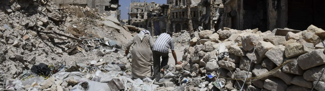 Two persons walk in the ruins of Aleppo