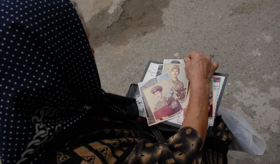 Azerbaijan, Shamkir. A mother looks through photographs of her missing son.